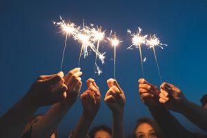 Many hands holding up sparklers representing Ignite Faith Niagara Leadership Development