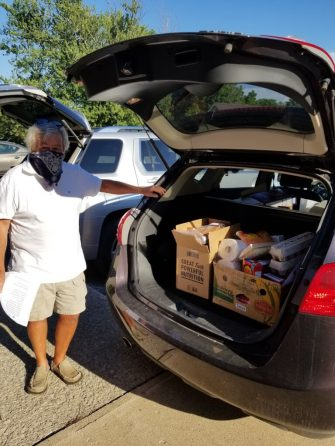 Woman standing behind vehicle with hatch open for Migrant Farmworkers Project